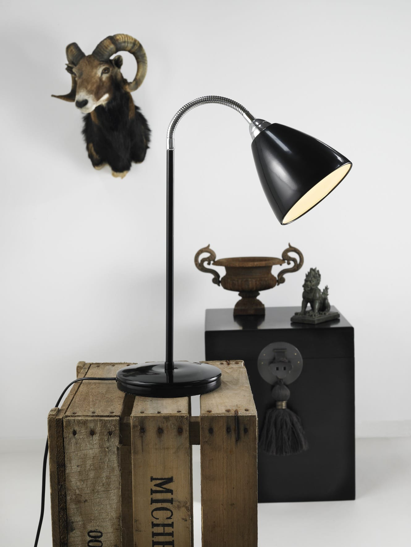 Black Task lamp sits on wooden crate eclectic mix of retro objects.